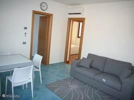 De woonkamer heeft een sofa die uitgetrokken kan worden voor een extra slaapplaats.