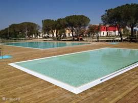 Een zwembad van 20 x 10 plus een kinderbad van 5 x 10 meter. Ligbedden en parasols staan eromheen.