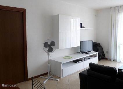 In de ruime woonkamer staan één driezits- en één tweezits bank, salontafel, een TV met ontvangst van de meeste populaire nederlandse zenders en een dvd-speler. Er zijn boeken, CD's, DVD's en info van de plaatselijke VVV aanwezig.