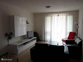 De woonkamer biedt toegang tot het balkon met terrasstoelen en een tafel. Op het balkon kun je genieten van de namiddag en avondzon.