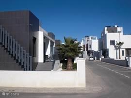 De straat waarin de woning staat met het zwembad direct voor de deur
