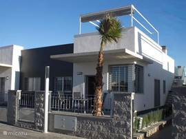 Mooi modern type woning met ruim dakterras waarop ligbedden, een luxe tuinset en een toldos.