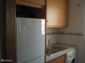 De keuken met aan de ene kant de koel/vries combinatie en de wasmachine