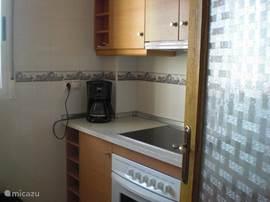 De keuken aan de andere kant met de elektrische kookplaat, de oven, afzuiging en koffiezetter
