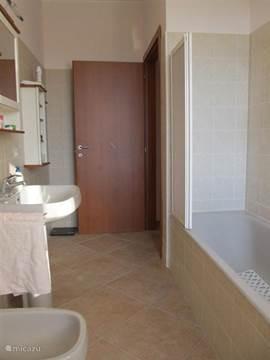 De badkamer op de eerste woonlaag met douche/ligbad, toilet en bidet. Hier is ook een wasmachine aanwezig.
