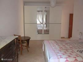 De 1e slaapkamer met een comfortabel 2-persoons bed en ruime garderobekasten.