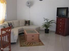 App B: ruime woonkamer met een grote lederen hoekbank,tv ,radio,wandventilator. De vloer is volledig betegeld.