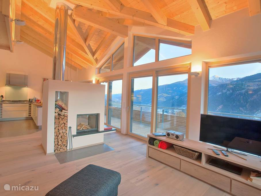 Spacious living room with high facade, fireplace, dining area and sitting area. Nice view on the roof.