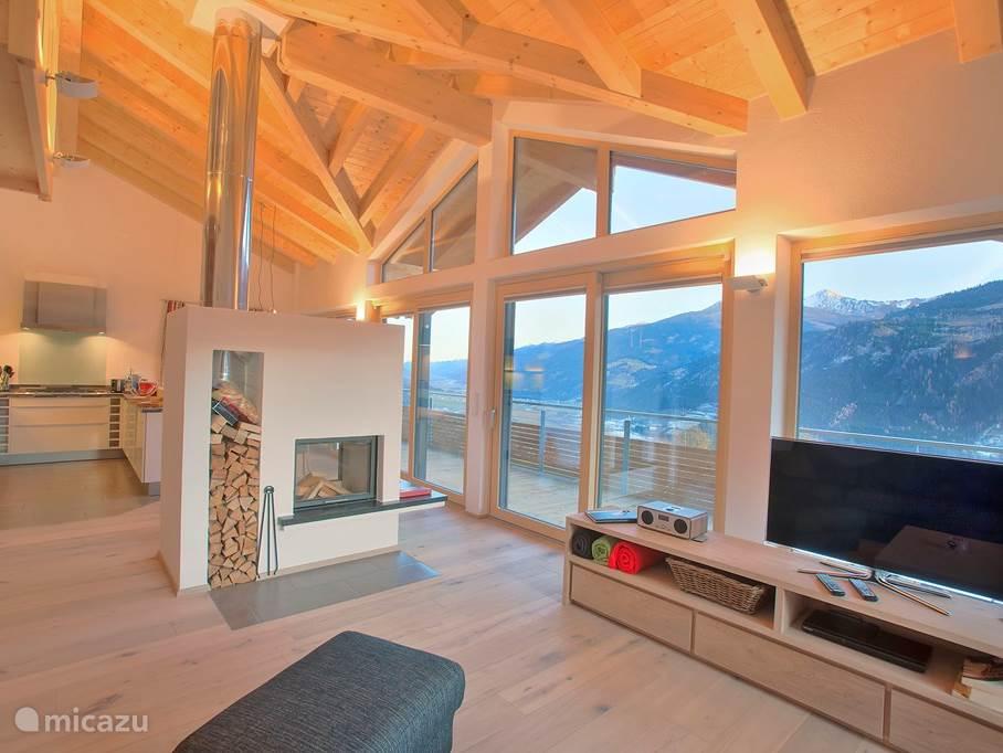 Ruime woonkamer met hoge pui, open haard,eethoek en zithoek. Mooi zicht op de dakconstructie.