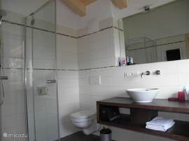 Bathroom with shower, toilet, double sinks, heated floor and towel rail.