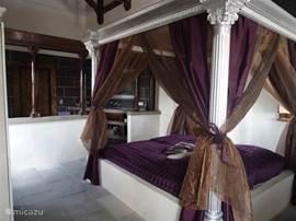 De slaapkamer met een zilveren hemelbed