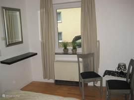 De andere zijde van de slaapkamer biedt u de mogelijkheid even te zitten of uw toilet te maken.