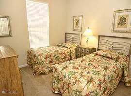 Een slaapkamer met twee aparte bedden. Ook hier een grote kast.