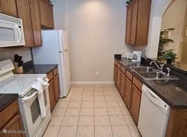 Een deels open keuken van alle gemakken voorzien. Gezellig contact met de woonkamer. Aan de rechterkant van de foto zie je de boog die de opening/bar van de open keuken vormt.