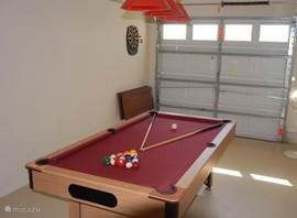 Een game-room met poolbiljart en dartbord.