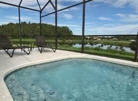 Het privé zwembad met heerlijke ligstoelen en mooi uitzicht op het meer.