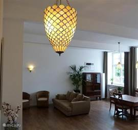 The living room is warmly decorated with modern kitchen, fireplace, cozy sitting area and dining table.