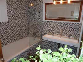 De luxe badkamer is voorzien van bad met douche, dubbele wastafel & toilet.