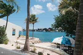 Uitzicht vanaf het zwembad. Dit is 1 van de strandjes en de steiger met trap. Zo kunt u ook een duik nemen in zee. U kunt zo een rondje zwemmen naar het strand en wat dacht u van snorkelen? ©xammes fotografie