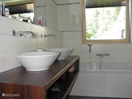 Spacious bathroom with bath, shower, toilet and 2 sinks.