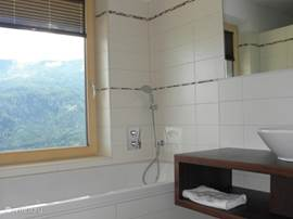 Spacious bathroom with bath, shower, toilet and sink in apartment Kristall. Enjoy the view!