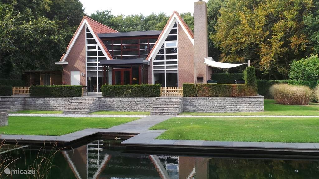 Achterzijde van de woning met deel van de zwemvijver