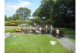 De zwemvijver biedt veel vertier en kan worden afgewisseld met de hottub.
