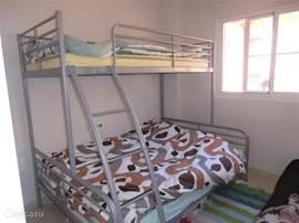 Op deze slaapkamer kunnen 3 personen slapen. Het onderste bed heeft een afm van 1.40x2.00m. In deze slaapkamer zit een muurkast met lades.