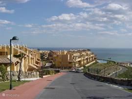 Dit is de 'oprit' van waaruit u naar het grote appartementencomplex rijdt. Een prachtig uitzicht over bergen en zee. Via deze weg rijdt u de ondergrondse parkeergarage binnen waar u een eigen parkeerplek heeft.