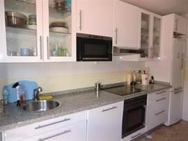 De keuken heeft een stenen werkblad. Vanuit de keuken ga je naar het washok waar de wasmachine staat.