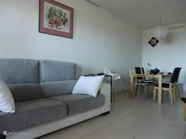 In de woonkamer staan een bank en losse fauteuils. Tevens staat er een (uitschuifbare) eettafel met 6 stoelen.