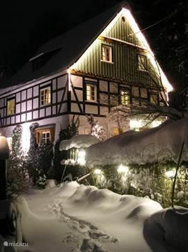 Haus im Wiesengrund met verlichting in de winter.