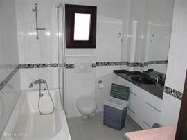 Centrale badkamer 1e verdieping met ligbad, toilet, wastafel en wasmachine.