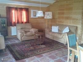 De gezellige ruime woonkamer met vloerverwarming, in jaren 50 stijl ingericht. We hebben zelfs een platenspeler en vinylplaten die u ouderwets kunt draaien! Veel ramen voor veel licht en veel uitzicht naar alle kanten! Natuurlijk is er ook een DVD speler, radio, TV met schotel antenne en Wifi.