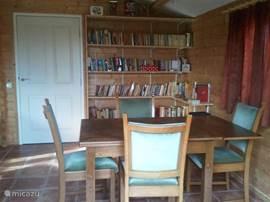 De gezellige eethoek met de prachtige jaren-50 stoelen en de bibliotheek.