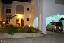 Sfeervolle vooraanzicht van villa Nyali in de avond.
