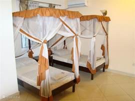 laapkamer in villa Nyali. Twee eenpersoons bedden met nachtkastjes en klampboe's. Ook is er een ruime ingebouwde kledingskast aanwezig.