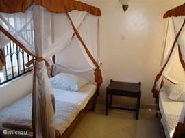 Ruime slaapkamer met twee eenpersoonsbedden met nachtkastjes en klamboe's. Ook is er een ruime ingebouwde kledingskast aanwezig.