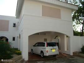 Vooraanzicht van het huis met een riante oprit en compacte mooie voortuin.