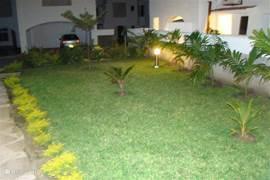 Aanzicht sfeervolle voortuin van Villa Nyali in de avond.