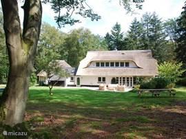 Dit prachtige rietgedekte landhuis ligt midden in het bos. De eerste buren bevinden zich honderden meters verderop. Aan de achterkant bevindt zich een groot grasveld. Direct aan het huis het terras met een mooie loungeset.
