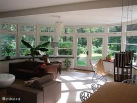 Een gedeelte van de woonkamer, met de serre. De begane grond bestaat uit een aantal ruimtes die met elkaar in verbinding staan en overal veel licht doorlaten.