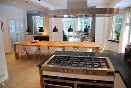 Dit is het eetgedeelte van de woonkamer, met de massieve, 4 meter lange 14-persoonstafel. Op de voorgrond een stukje van de open keuken.