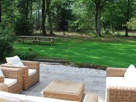 Het terras met de loungeset (die we in de winter wel opbergen). Daarachter het grasveld en uitzicht op het bos.