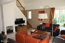 woonkamer met zicht op trap en open haard