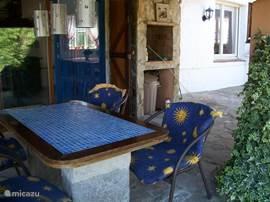 Overdekt terras met buiten-BBQ die vanuit de keuken door een schuifpui is te bereiken. Omringd door een romantische druivenrank.