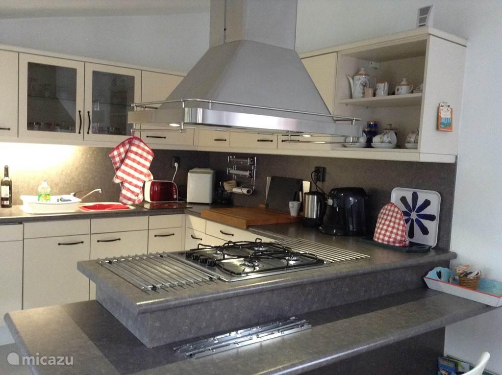 Moderne keuken met kookeiland en vaste apparatuur.