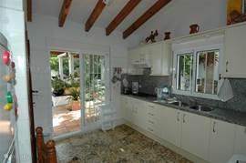 Ruime keuken met schuifdeuren naar de achtertuin met zwembad en pergola's.
