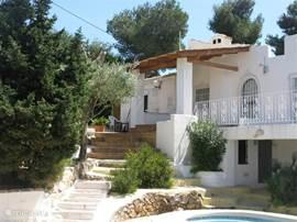 De villa, de terrassen en een tuin vol bomen en bloemen