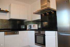 L-vormige dichte keuken met alle apparatuur